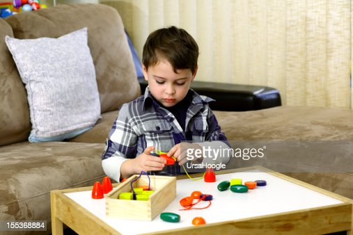 Best Toys For Autistic Boys : Autistic boy playing with colorful wooden beads stock