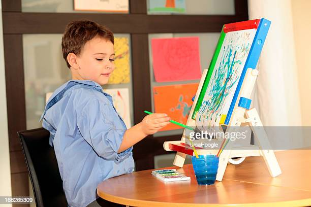 Autistic child painting with easel