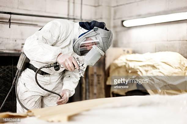 Auto body technician spray painting vehicle