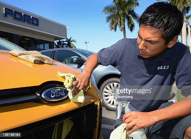 Auto detailer Chris Osorio cleans the grill of a 2012 Ford Motor Co Focus vehicle at a Maroone car dealership in Ft Lauderdale Florida US on...