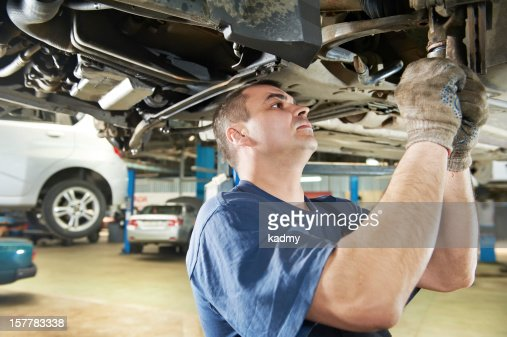 auto mechanic at car suspension repair work : Stock Photo
