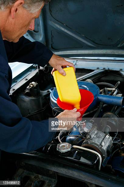 auto mechanic changing the oil