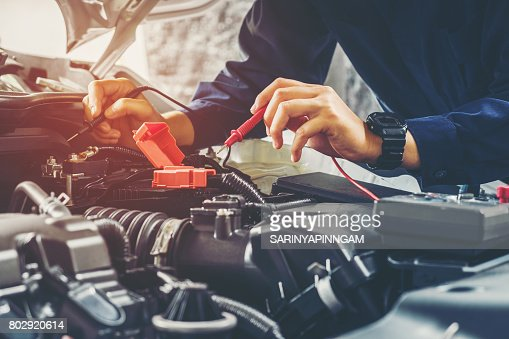 Auto mechanic checking car battery voltage : Stock Photo