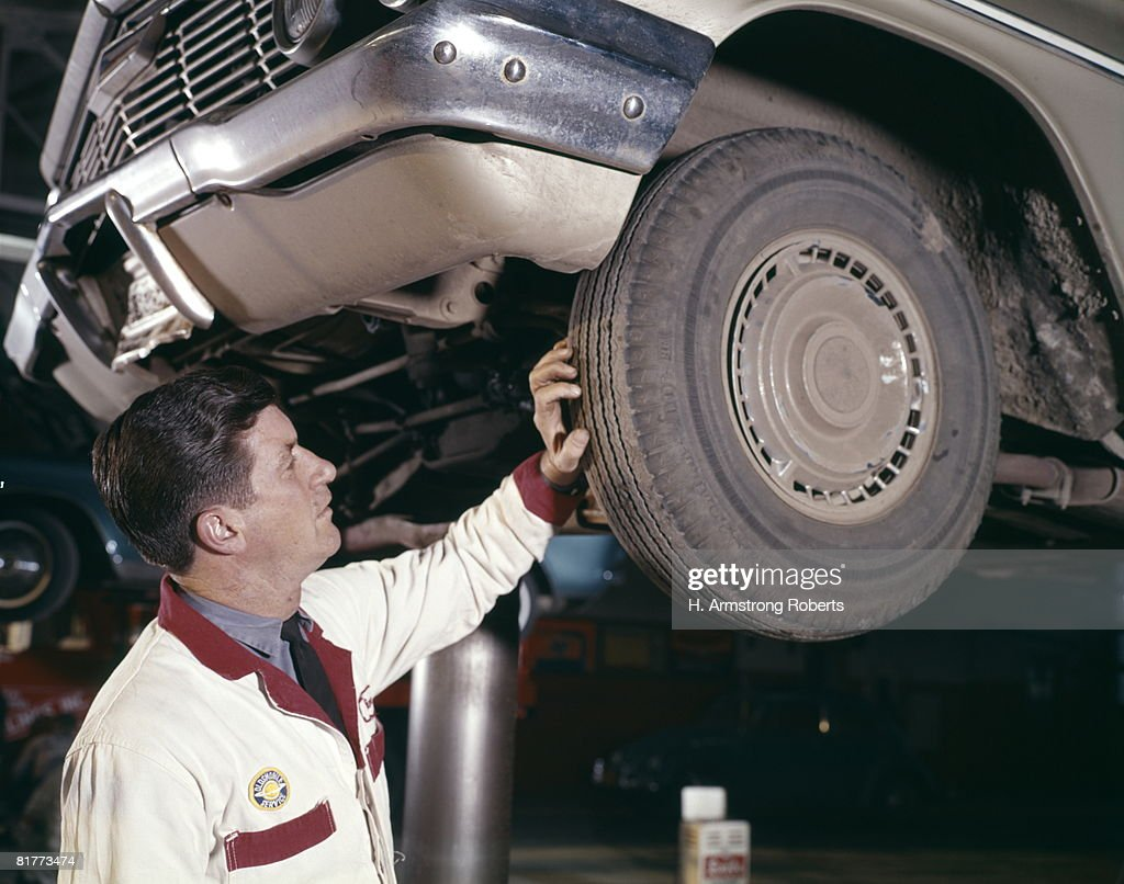 Auto Mechanic Man In Service Station, Checking Tread On Rubber Tire As Car Is On Gas Station Lift Rack. : Stock Photo