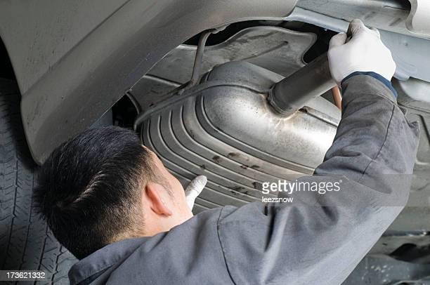 Auto Mechanic Removing Muffler