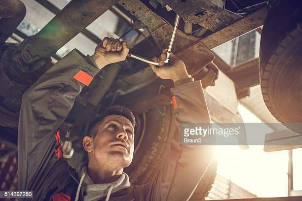 Auto mechanic repairing a chassis of a truck.