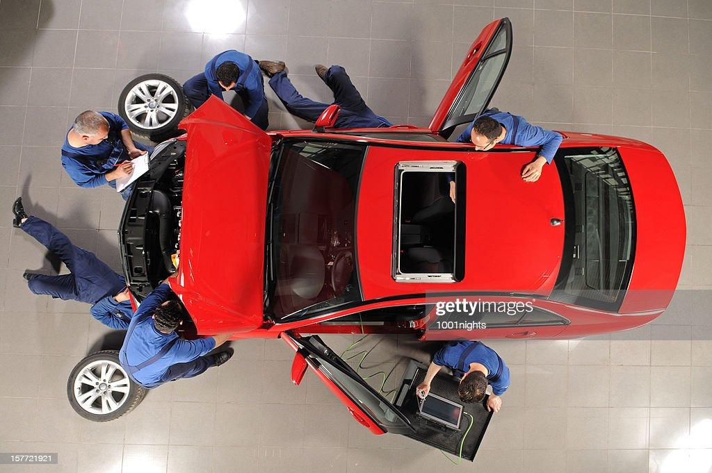 Auto mechanic team repairing the sports car : Stock Photo
