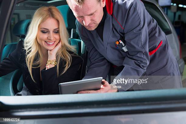 Auto mechanic with digital tablet talking to acute  customer