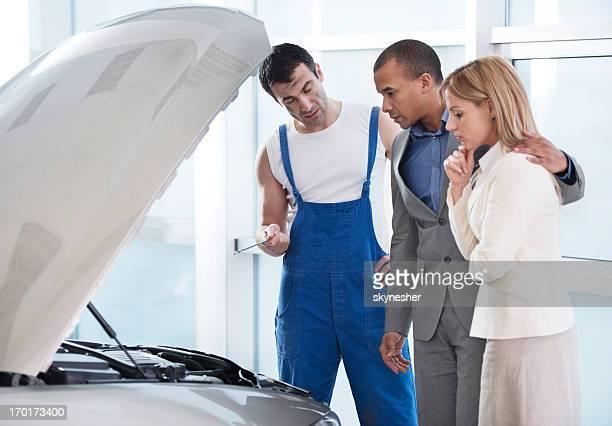 Auto-Mechaniker mit seinen Kunden
