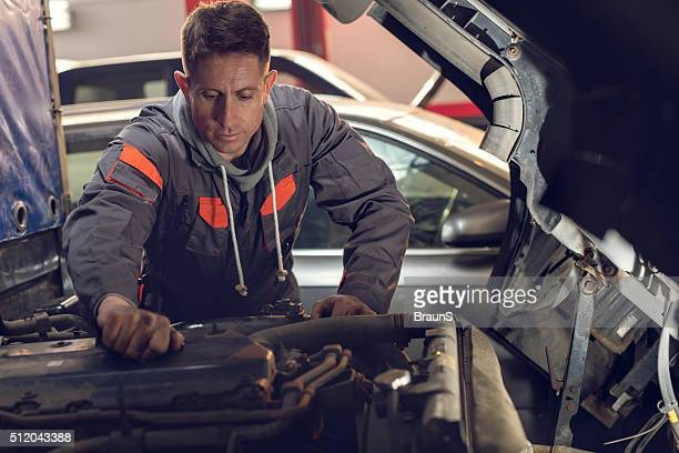 Mecánico de coches trabajando con un camión en una tienda de reparaciones.