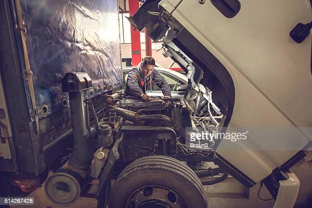 Mecánico de coches trabajando con un camión en Automático reparación.