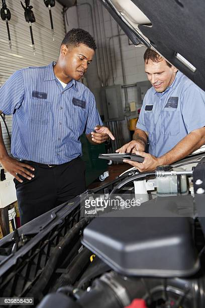 Auto mechanics in garage with digital tablet