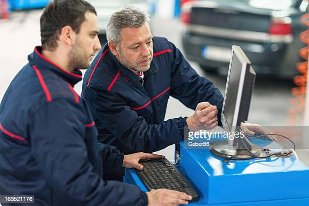 Auto mechanics working in repair shop