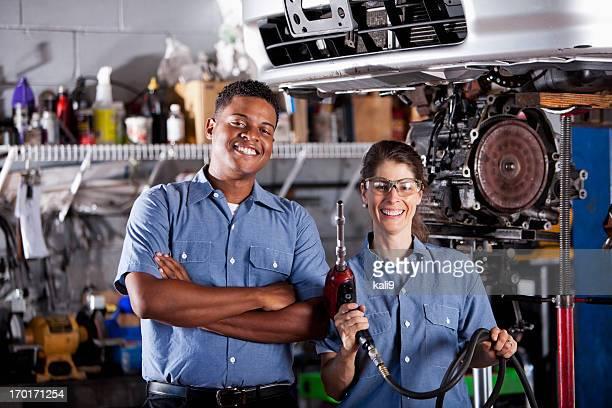 Auto mechanics working on car transmission