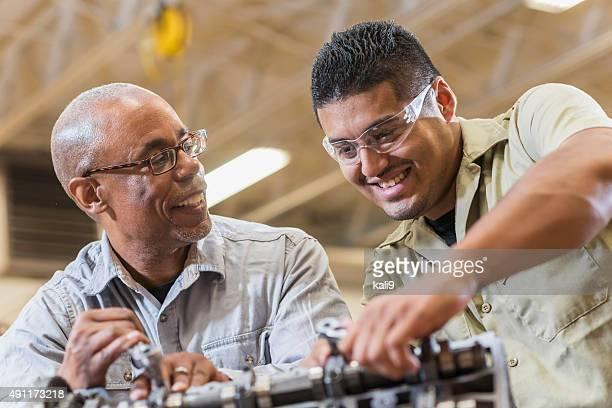 Auto mechanics working on gasoline engine