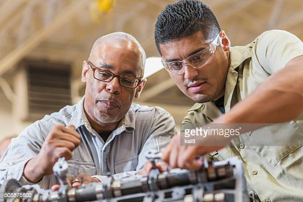 Auto mechanics working on gasoline engine