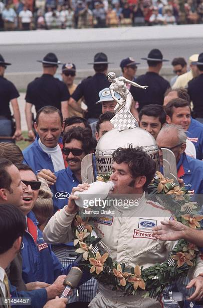 Auto Racing CART Indianapolis 500 Closeup of Al Unser Sr victorious with trophy and wreath drinking milk after winning race Indianapolis IN 5/31/1970
