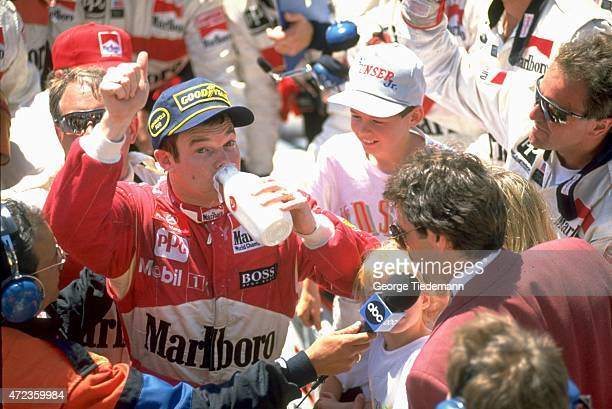 Indianapolis 500 Al Unser Jr victorious drinking milk and giving thumbs up sign in victory lane after winning race at Indianapolis Motor Speedway...
