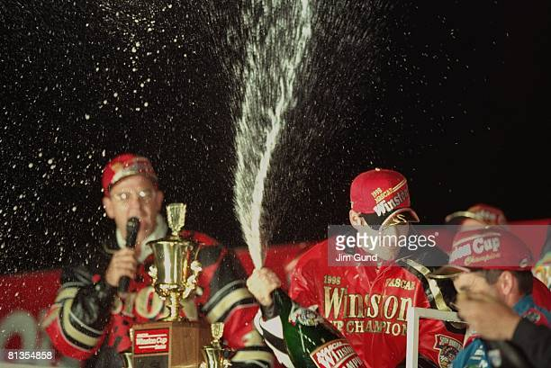 Auto Racing NASCAR NAPA 500 Jeff Gordon victorious with trophy and champagne after winning race and Winston Cup Hampton GA 11/8/1998