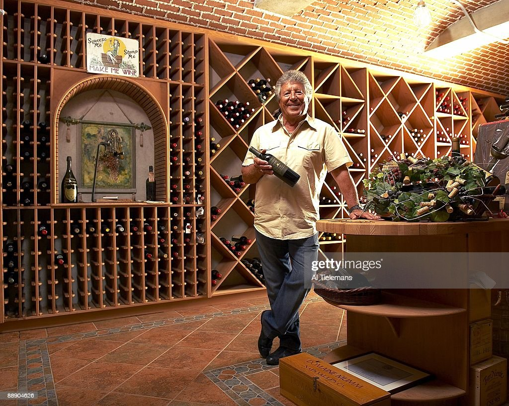 Portrait of former driver Mario Andretti holding a bottle of his Andretti Winery wine in cellar at his home Villa Montona. Nazareth, PA 5/13/2009