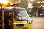 Auto rickshaw driver looking out of his vehicle across a park back lit by the sun, Kochi, India