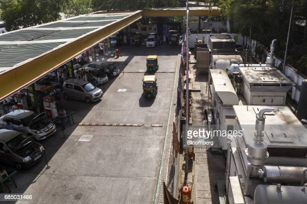 Auto rickshaws drive past vehicles being refueled with compressed natural gas at an Indraprastha Gas Ltd gas station in New Delhi India on Wednesday...