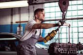 Image of auto workshop worker using engine hoist