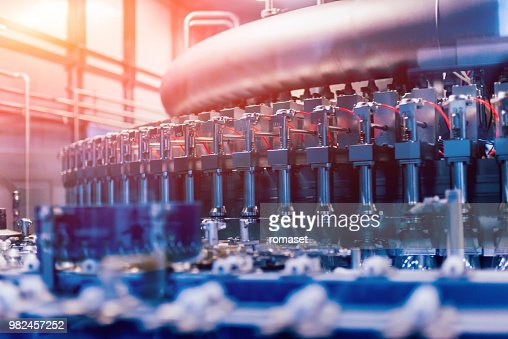 Automatic filling machine pours water into plastic PET bottles. Brewing production. : Stock Photo
