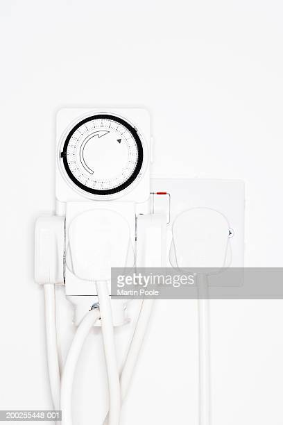 Automatic timer in overloaded plug socket on wall, close-up