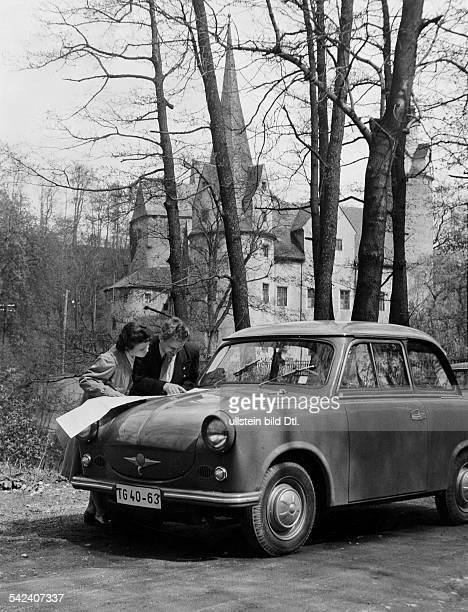 Automobile DDR Ehepaar mit neuem Trabant vor dörflicherKulisse beim Studium einer Strassenkarte 1958