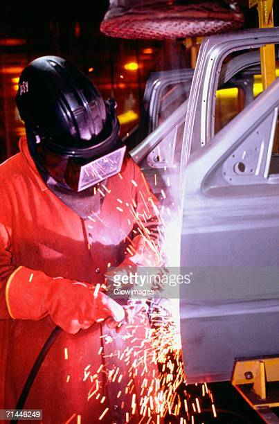 Automobile factory mechanic working on chassis in a shower of sparks