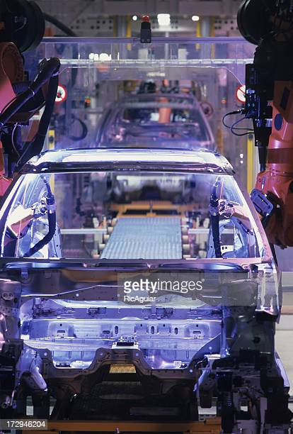 Automobile factory with cars being built on assembly line