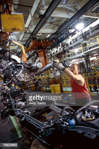 Automobile factory worker installing engine