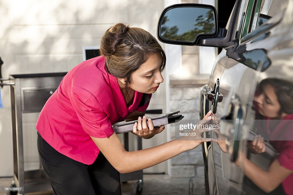 Automobile insurance adjuster inspecting damage to vehicle : Stock Photo