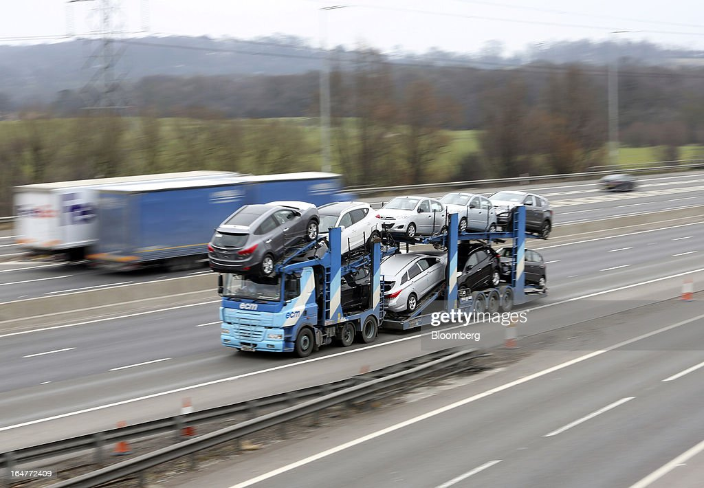 A automobile transporter carries vehicles along the northern section of the M25 motorway near London, U.K., on Wednesday, March 27, 2013. The U.K. government will increase spending on infrastructure projects, including road construction, by an annual 3 billion pounds ($4.6 billion) from 2015 as Chancellor George Osborne seeks to boost economic growth. Photographer: Chris Ratcliffe/Bloomberg via Getty Images