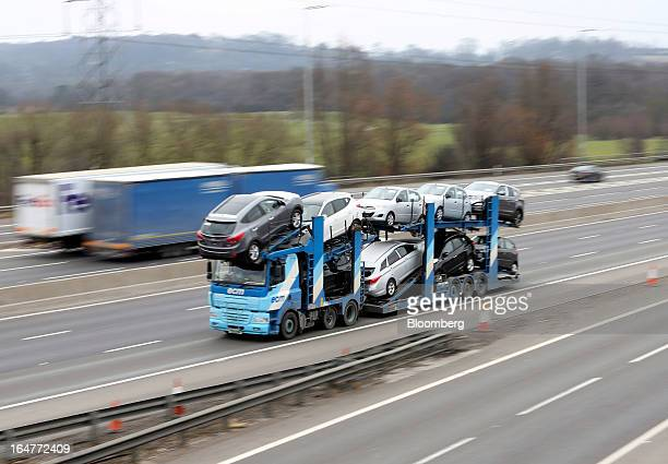 A automobile transporter carries vehicles along the northern section of the M25 motorway near London UK on Wednesday March 27 2013 The UK government...
