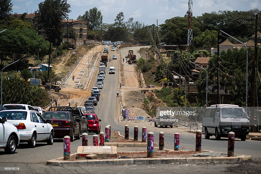 Automobiles are seen near a road under construction, right, in Nairobi, Kenya, on Friday, March 1, 2013. Next week's presidential vote will be the first since disputed elections in 2007 triggered ethnic fighting in which more than 1,100 people died and another 350,000 fled their homes. Photographer: Trevor Snapp/Bloomberg via Getty Images