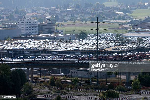 Automobiles including brands from VW Volkswagen AG Audi AG And Skoda AS are seen stacked on freight transporters at the Swiss auto distributor AMAG a...