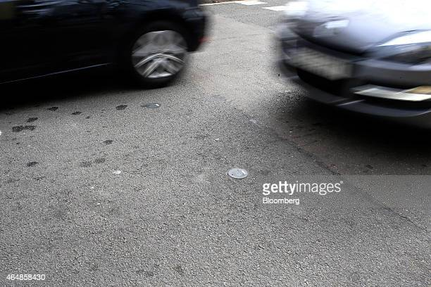 Automobiles pass a traffic volume sensor embedded in a road in Barcelona Spain on Wednesday Feb 25 2015 As executives from the world's biggest phone...