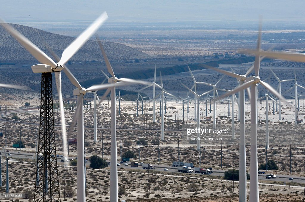 Automobiles pass by giant wind turbines powered by strong winds on March 27, 2013 in Palm Springs, California. According to reports, California continues its lead in green technology and has the lowest GHG emissions per capita, in the Nation.