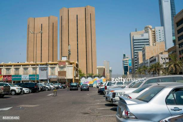 Automobiles stand in a parking lot near retail stores and office towers in Kuwait City Kuwait on Sunday Aug 13 2017 Kuwait will issue a tender to...