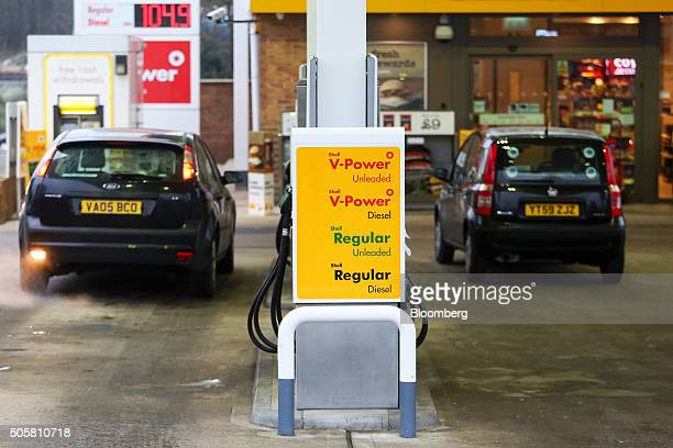 Automobiles stand next to petrol pumps on the forecourt of a Royal Dutch Shell Plc gas station in Brentwood UK on Wednesday Jan 20 2016 Shell which...