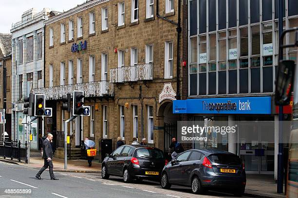 Automobiles stand parked outside the entrance to a CoOperative Bank Plc branch in Huddersfield UK on Wednesday May 7 2014 Former CoOperative Bank...