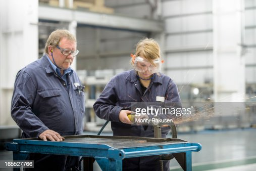 Automotive apprentice and tutor using machinery, wearing boiler suits and protective goggles in car plant