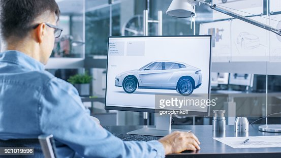 Automotive Engineer Works on the Personal Computer, He Perfects New Car Model Prototype Sketch. He Works in the Bright and Modern Office. : Stock Photo