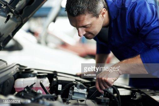 Automotive specialist adjusting an engine