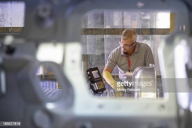 Automotive worker testing welding on car body in car plant
