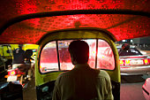 Autorickshaw taxi driving in evening traffic, rear view