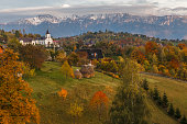Autumn alpine landscape, famous alpine village with spectacular gardens and high snowy mountains in background near Bran, Magura, Transylvania, Romania.
