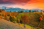 Beautiful autumn alpine landscape, famous alpine village with stunning colorful clouds and high snowy mountains in background near Bran, Magura village, Transylvania, Romania, Europe